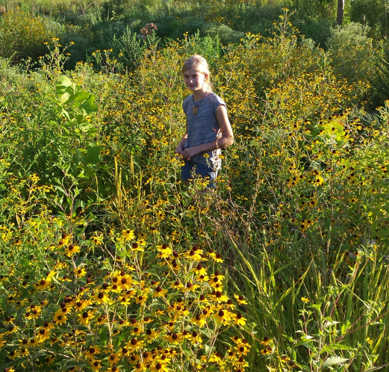 Young girl standing amongst native landscape