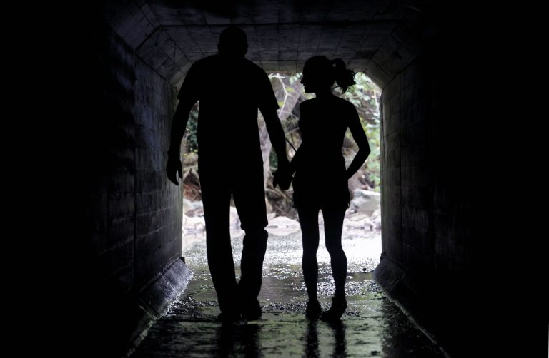 2 people, holding hands, walking in a tunnel waterway